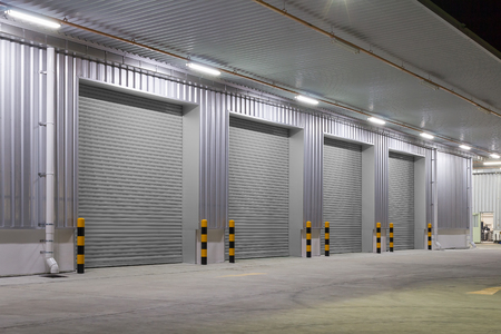 Shutter door or roller door and concrete floor outside factory building  for industrial background. Imagens