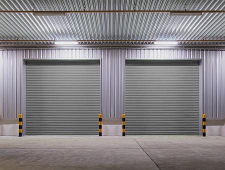 Puerta de persiana o puerta enrollable y piso de concreto fuera del uso del edificio de la fábrica para el fondo industrial.