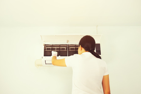 Woman cleaning air conditioner inside room. Stockfoto - 122781657