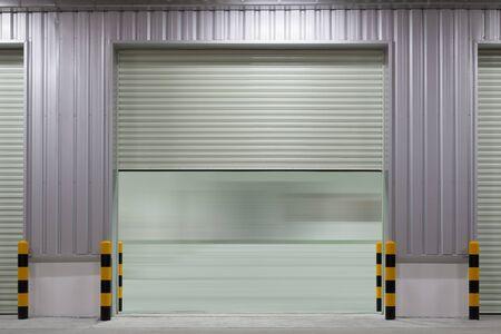 Porta dell'otturatore o porta a rulli e pavimento in cemento all'esterno della costruzione di una fabbrica per uso industriale
