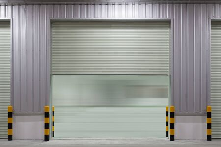 Rolltor oder Rolltor und Betonboden außerhalb des Fabrikgebäudes für industriellen Hintergrund.