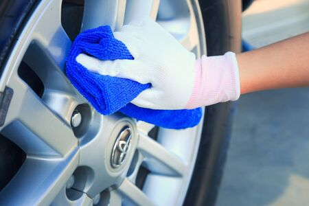 Woman worker cleaning and waxing car wheels. Stock Photo