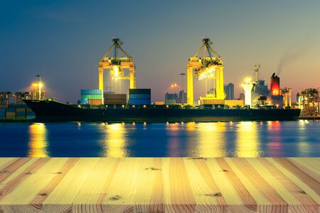 Cargo ship and crane at port, twilight time.