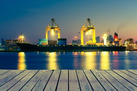 Le cargo et la grue au port réfléchissent sur la rivière, au crépuscule.