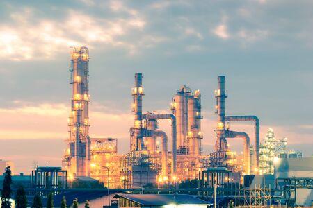 Réservoir de distillation de l'usine de raffinerie de pétrole au crépuscule. Banque d'images