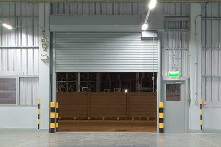 Open shutter door interior and concrete floor, night time. Stockfoto