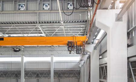 Overhead crane and hook on steel beam with factory wall background. Zdjęcie Seryjne