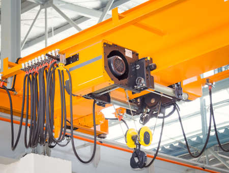 Overhead crane and hook on steel beam with factory wall background.