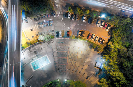 People in park, garden. Public place and space for recreation activity in Chiang Mai of Thailand i.e. aerobic dancing, takraw, relax, exercise, workout. With car, car park lot and line in aerial view. 版權商用圖片