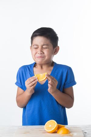 acidic: Asian child with a pout biting sour lemon. Sour taste. Stock Photo