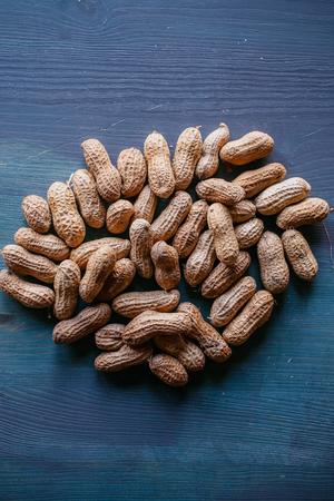 쉘 텍스처 및 배경에서 땅콩입니다. 땅콩 질감입니다. 껍질을 벗긴 땅콩. 건강한 음식. 나무 배경에서 껍질 된 땅콩의 뷰를 닫습니다. 추상적 인 배경