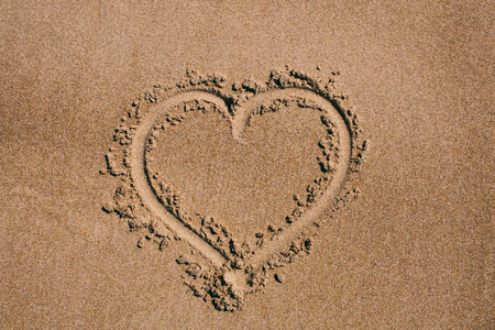 Heart drawn in the sand. Beach background with heart drawing. Heart shape love symbol as background. Love concept. 스톡 콘텐츠