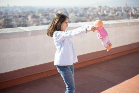 Little girl playing with a doll on the rooftop Stockfoto