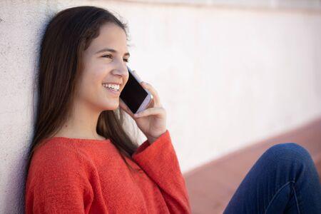 Happy teenage girl talking by mobile phone sitting in roof Stockfoto
