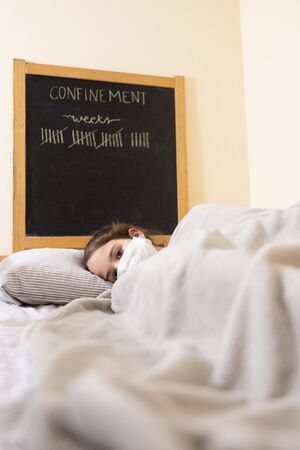 Covid 19 sick girl in bed with face mask Foto de archivo