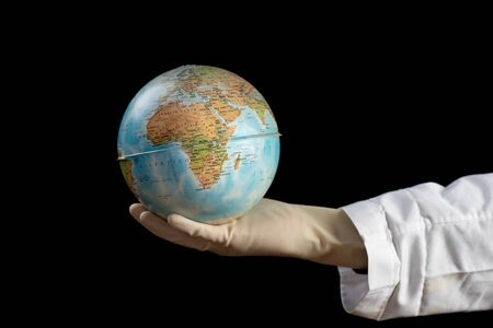 Doctor hand holding a world globe with his hand on black background Foto de archivo