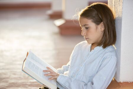 Concentrated girl reading a book sitting outdoors