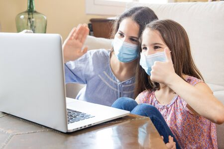 Two sisters in protective mask making a video call in the living room of their home