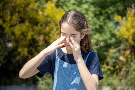 Little girl affected by an allergy rubbing her itchy eyes in the garden