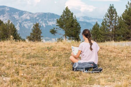 hiker girl sitting on the meadow looking at the route on a map Stock Photo