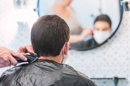 Boy defocuses through the mirror with protective mask while his mother shaves his hair at home Standard-Bild