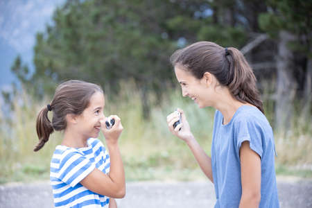 Two happy sisters very close talking and joking with a walkie-talkie