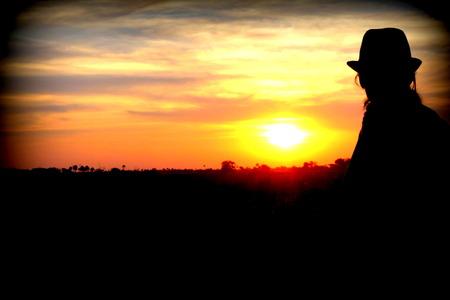 okavango delta: Relaxed young woman amazed in front of a wonderful sunset in Okavango Delta, Botswana