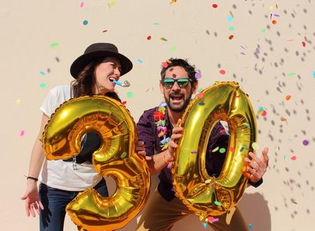 compleanno: Allegro paio festeggia un compleanno trent'anni con grandi palloncini d'oro e il colorato pezzi di carta nell'aria.
