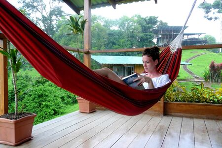 Young woman reading a book on a hammock in Fincas Maresia lodge, Bahia Drake, Corcovado National Park, Costa Rica