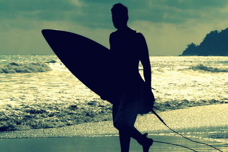 Silhouette of surfer with a board on a sunset evening in Manuel Antonios National Park main beach, Costa Rica