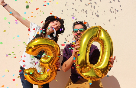 s horn: Cheerful couple celebrates a thirty years birthday with big golden balloons and colorful little pieces of paper in the air.