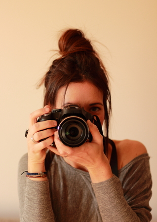 camera: Young female photographer with camera on soft background taking a picture with her pretty new device