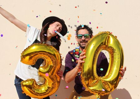 adult birthday party: Cheerful couple celebrates a thirty years birthday with big golden balloons and colorful little pieces of paper in the air.