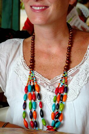 viejo: Close up of a wooden necklace worn by a cheerful young woman in Puerto Viejo, Costa Rica.