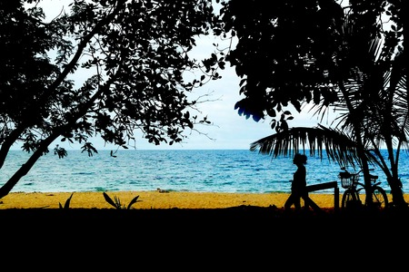 viejo: A young female hiker, rests and enjoys the view after a long bicycle ride to Punta Uva beach at Puerto Viejo, Costa Rica Stock Photo