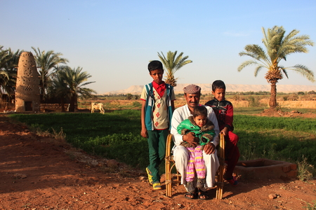 egypt: Dahla Oasis, Egypt - April 2nd of 2015: A bedouin family posing in front of the camera with their own land backwards. During centuries bedouin society has ruled in the western egyptian desert. Editorial