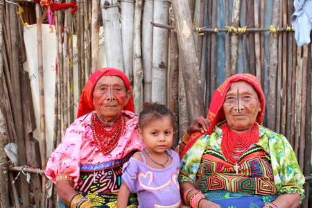 Playn Chico village, Panama - August, 4, 2014: Three generations of kuna indian women in native attire sell handcraft clothes to travelers and tourists, kun aindians territory, San Blas region, Panama.