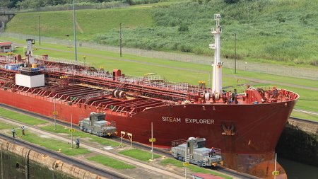 allowing: Miraflores locks, Panama - August 5th of 2014: Red large cargo ship entering Miraflores Locks, where vessels are lifted or lowered 54 feet 16.5 m allowing them to go from Pacific to Caribbean Sea.