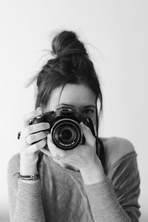 human photography: Young female photographer with camera on soft background taking a picture with her pretty new device