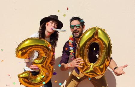 persona alegre: Pareja alegre celebra su cumpleaños treinta años con grandes globos de oro y coloridos pequeños trozos de papel en el aire.
