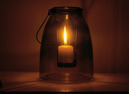 recipient: Closeup of a burning candle placed inside an ancient glass recipient.