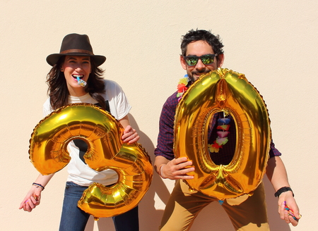 thirty: Cheerful couple celebrates a thirty years birthday with big golden balloons and colorful little pieces of paper in the air.