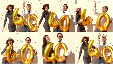 happy young: Cheerful couple celebrates a forty years birthday with big golden balloons and colorful little pieces of paper in the air. Stock Photo