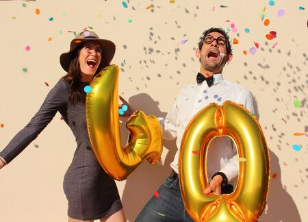 photo people: Cheerful couple celebrates a forty years birthday with big golden balloons and colorful little pieces of paper in the air. Stock Photo