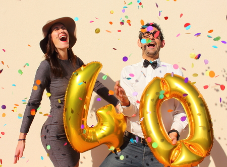 young people party: Cheerful couple celebrates a forty years birthday with big golden balloons and colorful little pieces of paper in the air. Stock Photo