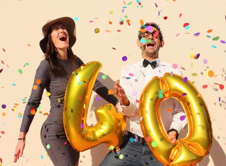 Vrolijk paar viert veertig jaar verjaardag met grote gouden ballonnen en kleurrijke kleine stukjes papier in de lucht. Stockfoto - 47993222