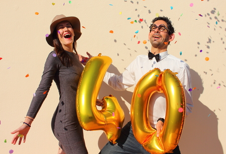forty: Cheerful couple celebrates a forty years birthday with big golden balloons and colorful little pieces of paper in the air. Stock Photo