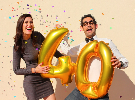 Cheerful couple celebrates a forty years birthday with big golden balloons and colorful little pieces of paper in the air. Stock Photo