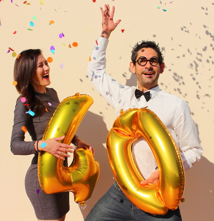adult birthday party: Cheerful couple celebrates a forty years birthday with big golden balloons and colorful little pieces of paper in the air. Stock Photo