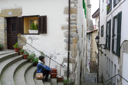 basque woman: Young woman relaxing on Hondarribia old village streets during a winter morning walk, Basque Country, Spain Stock Photo